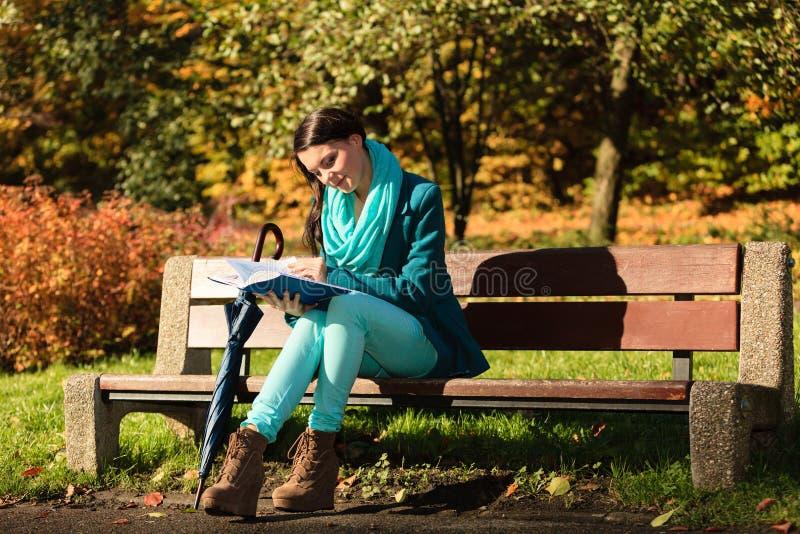 Ragazza che si rilassa in libro di lettura autunnale del parco Caduta fotografia stock libera da diritti