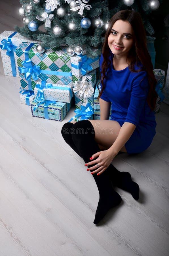 Ragazza che si siede con i regali sotto l'albero di Natale fotografia stock libera da diritti
