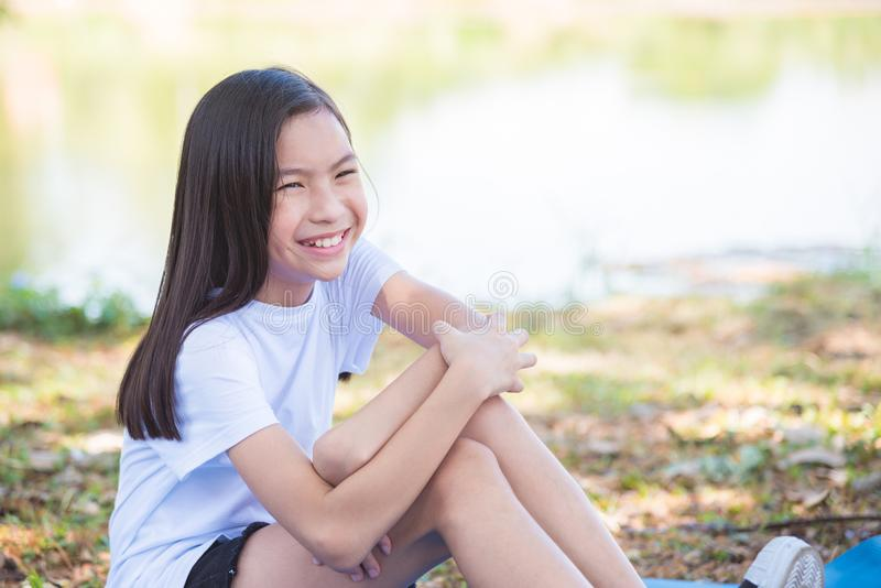 Ragazza che si siede e che sorride nel parco fotografia stock