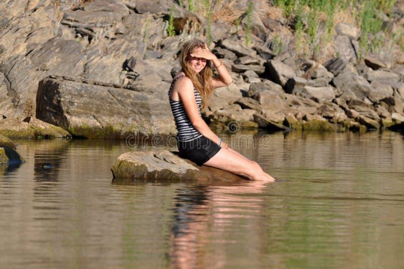 Ragazza che si siede nel lago fotografia stock libera da diritti