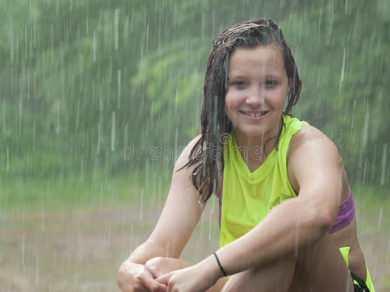 Ragazza che si siede nella pioggia fotografia stock