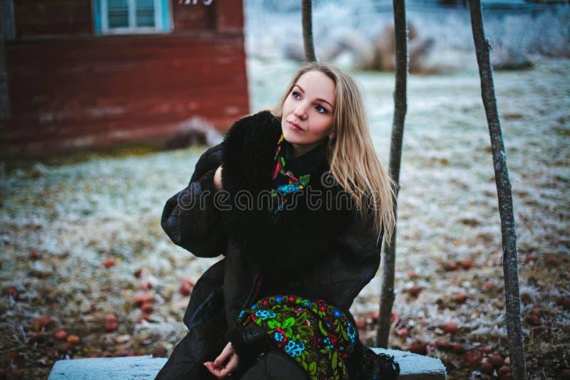 Ragazza che si siede su un banco nel vill fotografia stock