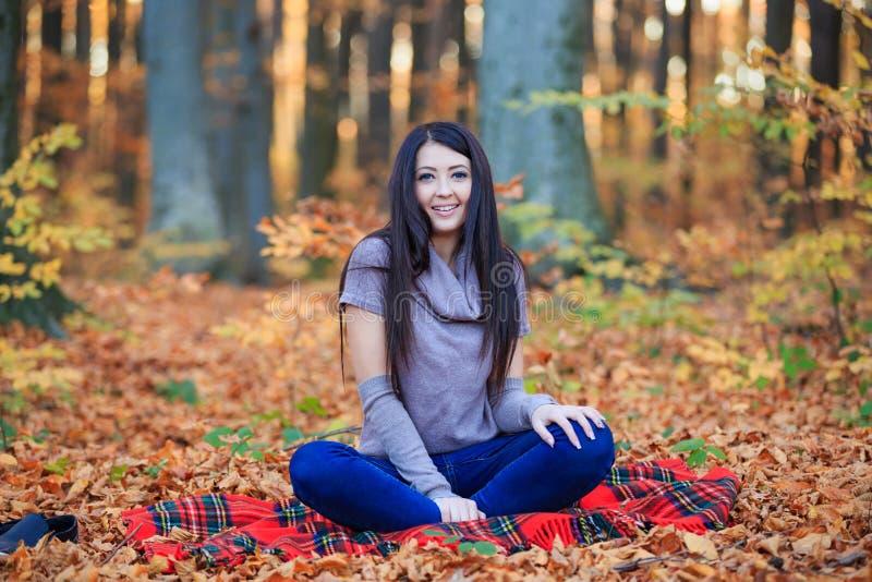 Ragazza che si siede su una coperta fotografia stock