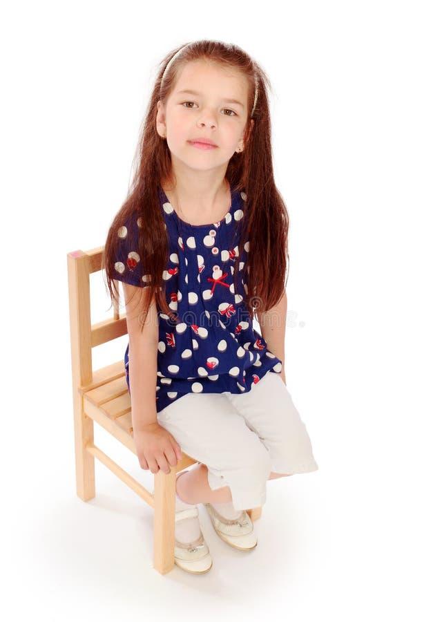 Ragazza che si siede su una piccola sedia fotografia stock