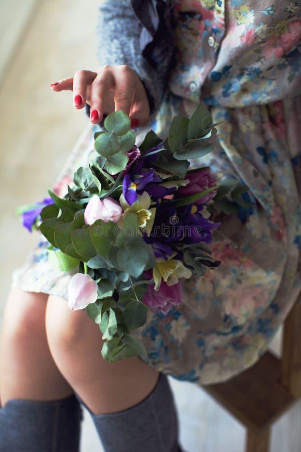 Ragazza che si siede su una sedia e che tiene un mazzo dei fiori in lei fotografia stock libera da diritti
