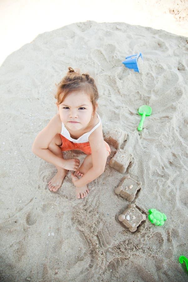 Ragazza che si siede su una spiaggia fotografia stock libera da diritti