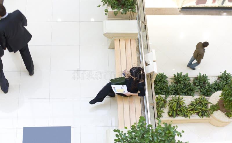 Ragazza che si siede sul banco e che legge uno scomparto fotografia stock