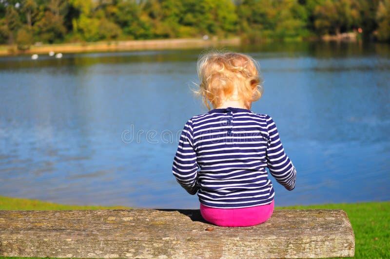 Ragazza che si siede sul lago di trascuratezza del banco immagini stock libere da diritti