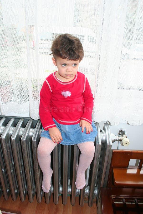 Ragazza che si siede sul sistema di riscaldamento fotografie stock libere da diritti