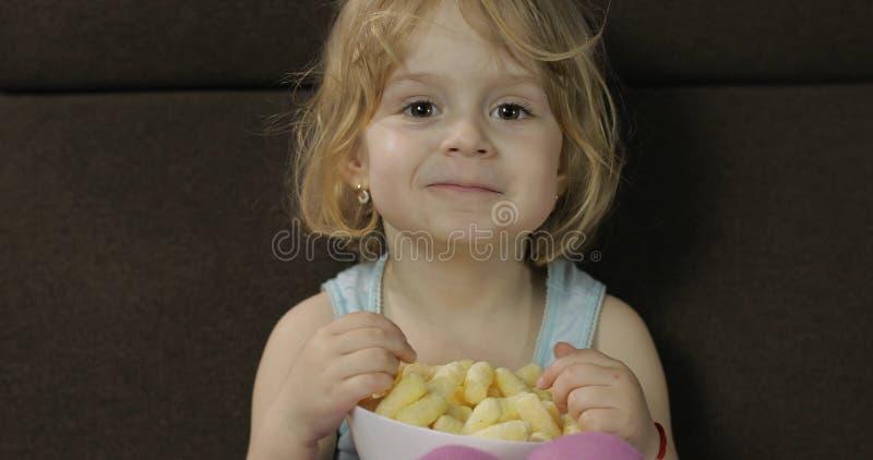 Ragazza che si siede sul sof? e che mangia i soffi del cereale Puffcorns di gusto del bambino fotografie stock libere da diritti