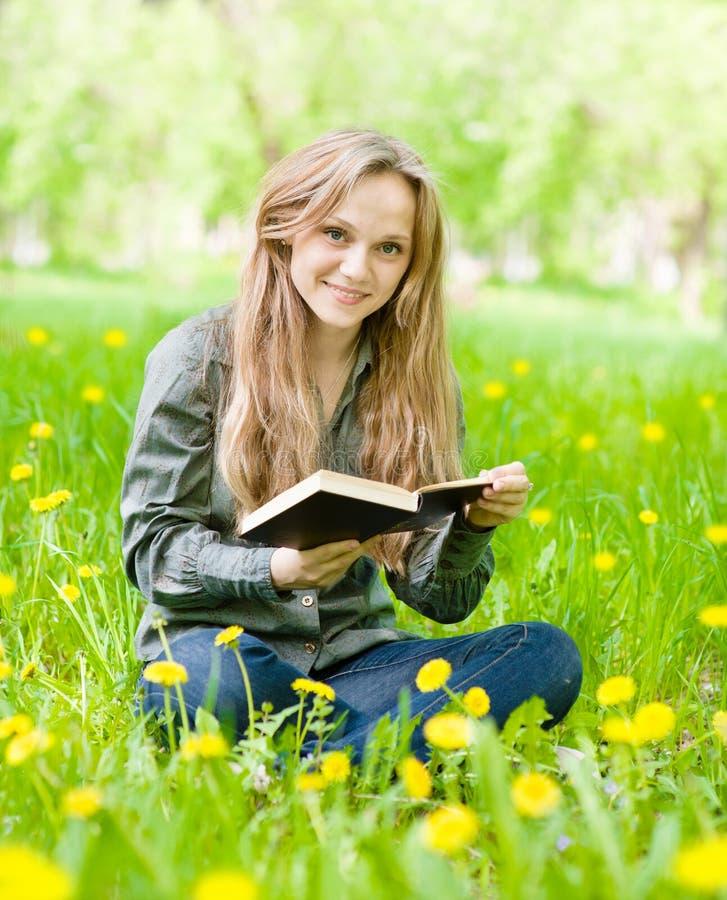 Ragazza che si siede sull'erba con i denti di leone che legge un libro fotografie stock