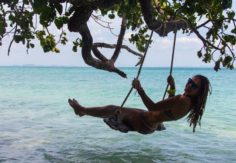 Ragazza che si siede sull'oscillazione, spiaggia tropicale fotografie stock