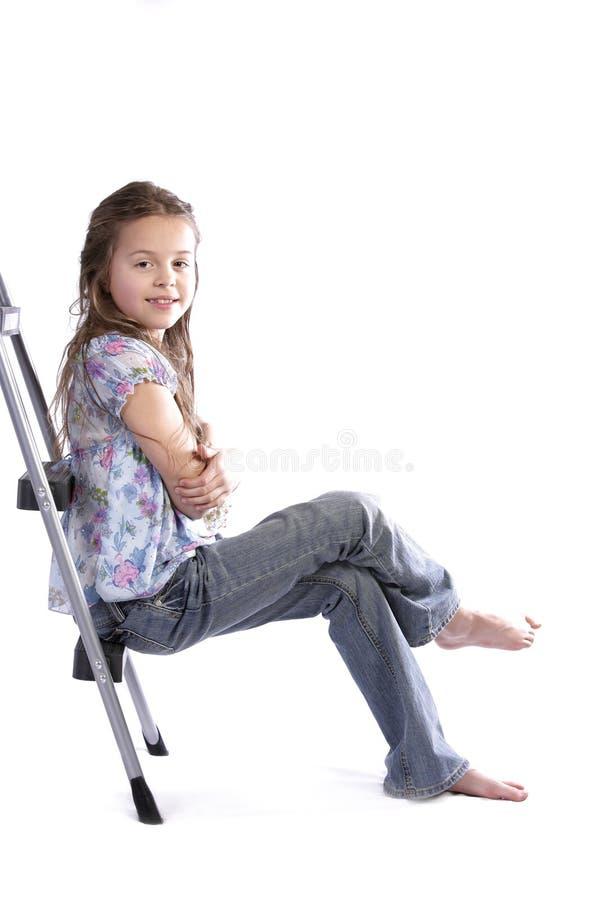 Ragazza che si siede sulla scaletta fotografie stock libere da diritti