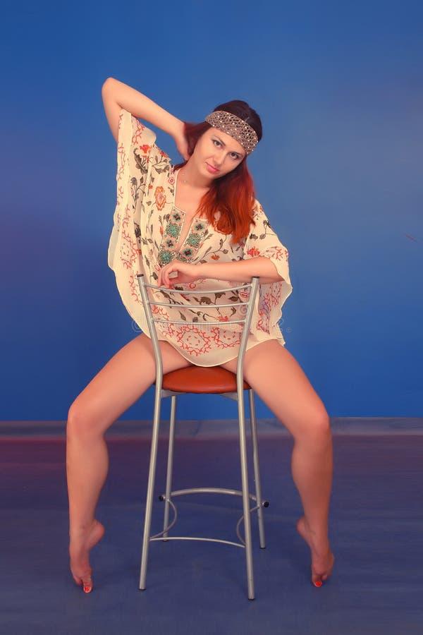 Ragazza che si siede sulla sedia con le gambe lunghe a parte fotografia stock libera da diritti