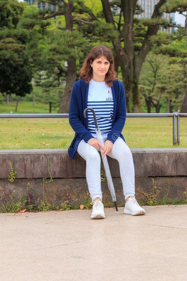 Ragazza che si siede sulla via a Tokyo immagine stock libera da diritti