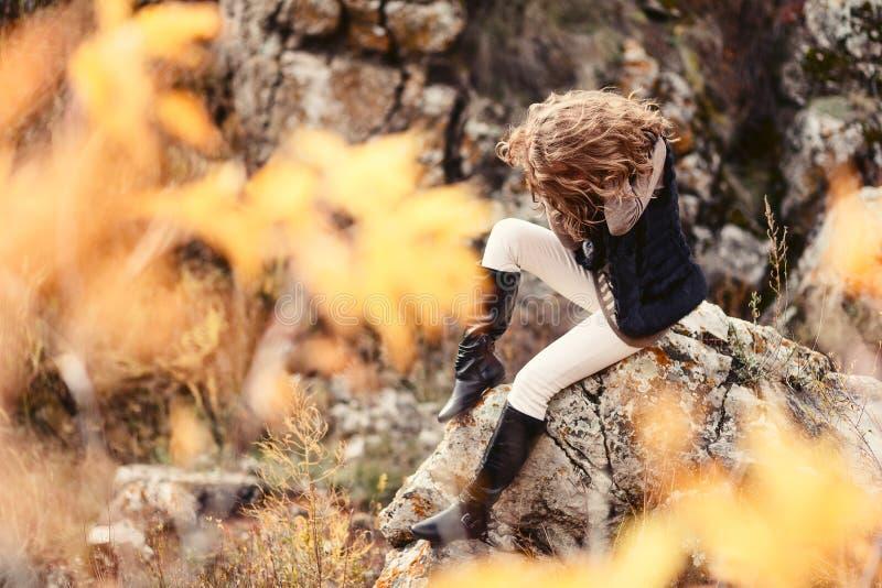 Ragazza che si siede sulle rocce, coperte di capelli spessi immagini stock