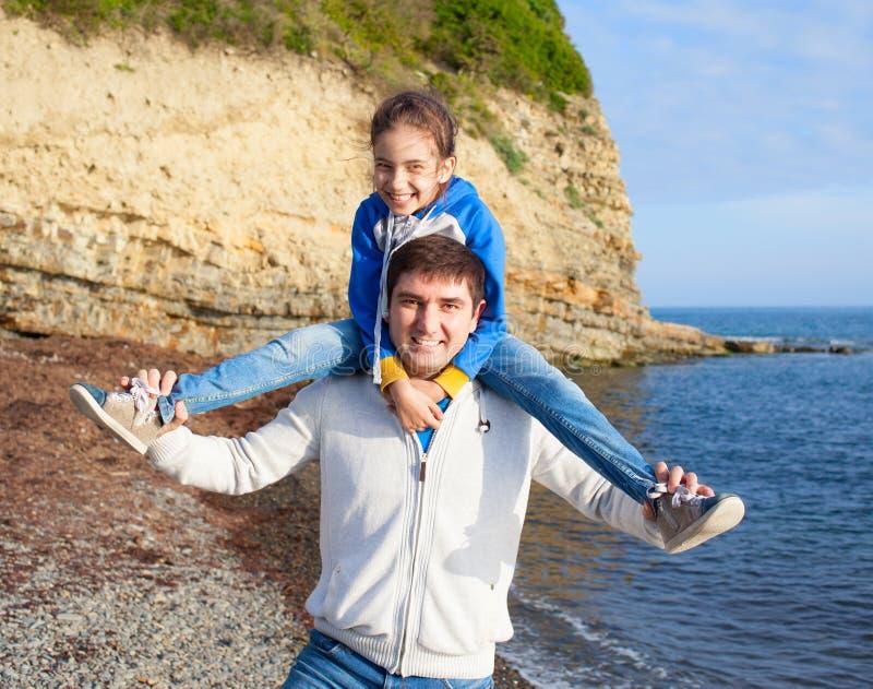 Ragazza che si siede sulle spalle del papà sul fondo del mare fotografie stock libere da diritti