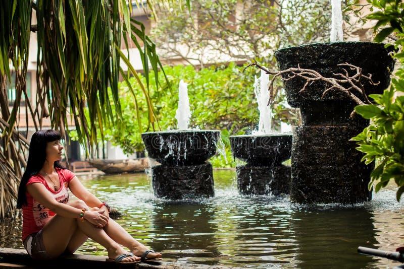 Ragazza che si siede in un parco esotico fra le fontane concetto di corsa Vista posteriore donna che esamina cascata nell'hotel fotografia stock libera da diritti
