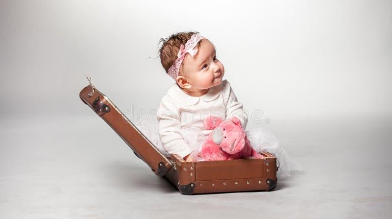 Ragazza che si siede in valigia con l'orsacchiotto rosa immagini stock libere da diritti