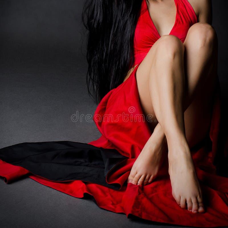 Ragazza che si siede in vestito rosso fotografia stock libera da diritti