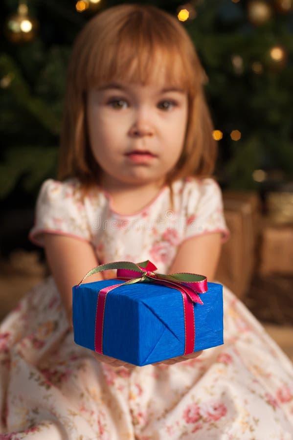 Ragazza che si siede vicino all'albero di Natale con il contenitore di regalo fotografia stock libera da diritti