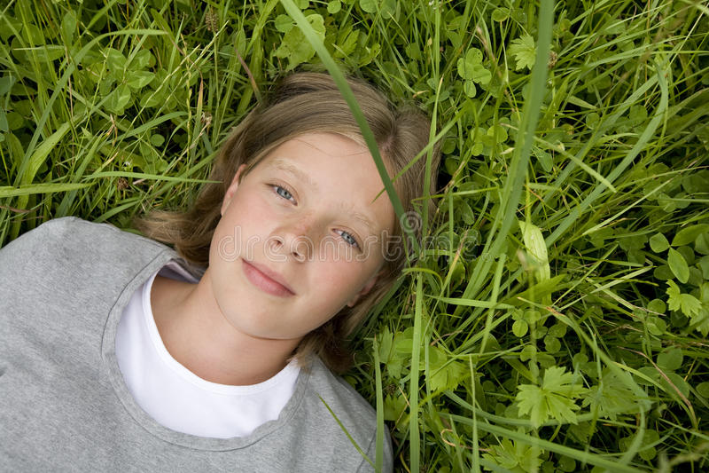 Ragazza che si trova nell'erba che sogna di? fotografia stock libera da diritti