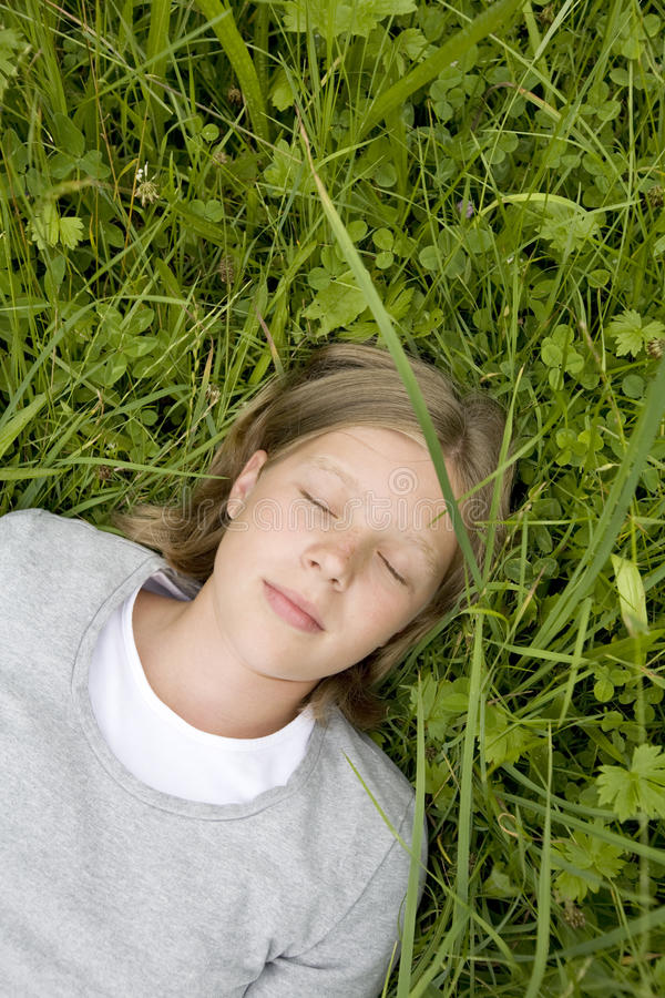Ragazza che si trova nell'erba che sogna di? fotografie stock