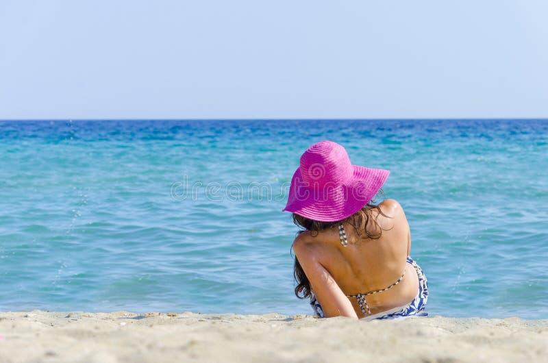 Ragazza che si trova nella sabbia della spiaggia fotografia stock