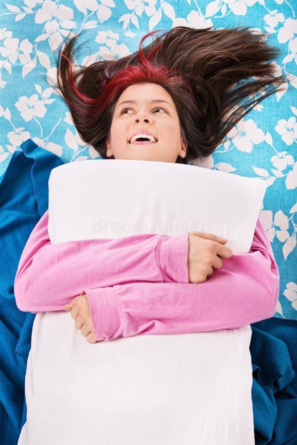 Ragazza che si trova sul suo letto che abbraccia un cuscino fotografie stock libere da diritti