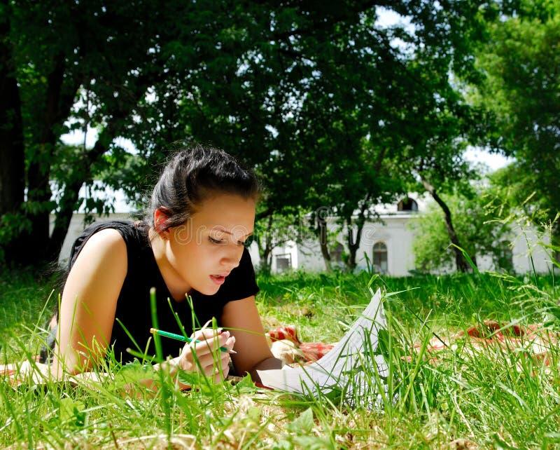 Ragazza che si trova sull'erba e sull'apprendimento immagini stock