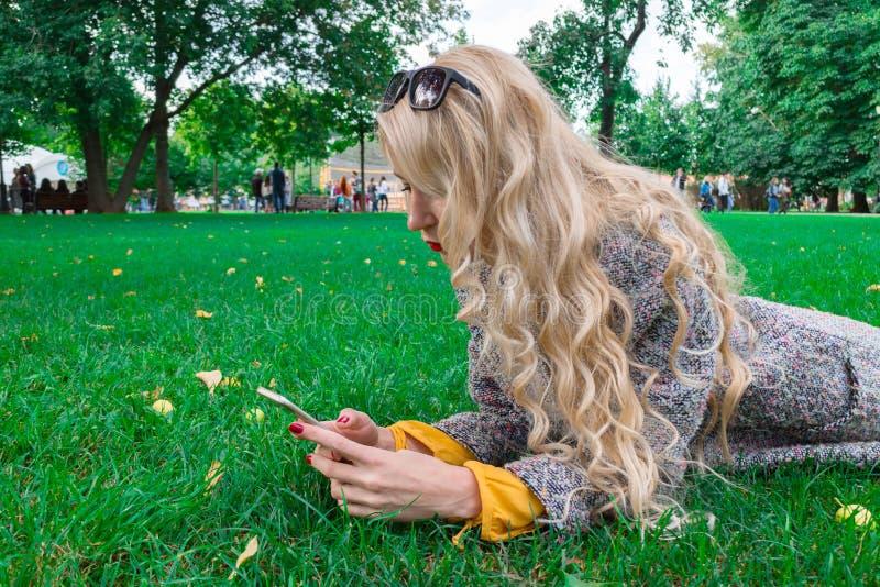 Ragazza che si trova sull'erba nel parco di autunno, tenente uno smartphone immagini stock