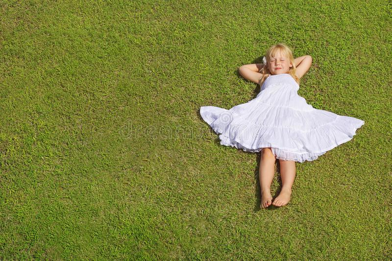 Ragazza che si trova sull'erba verde, vista superiore del bello bambino immagine stock