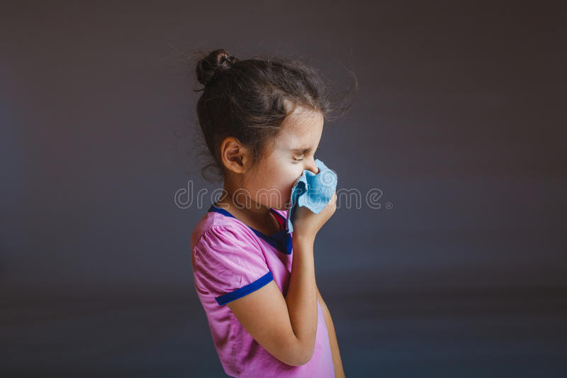 Ragazza che soffia il suo naso nel fazzoletto su un gray fotografia stock libera da diritti