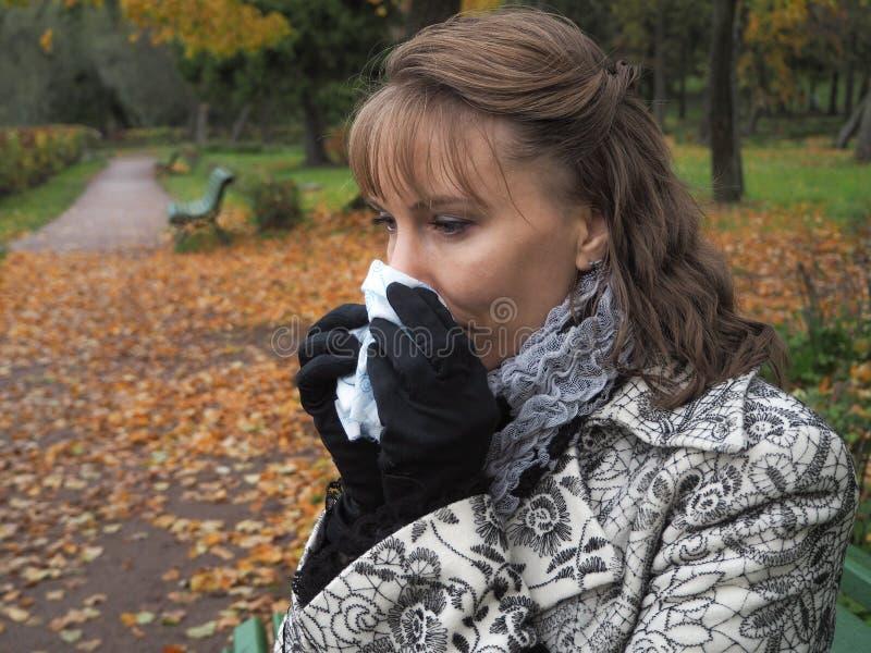 Ragazza che soffia il suo naso in un fazzoletto di carta nel parco di autunno fotografie stock libere da diritti