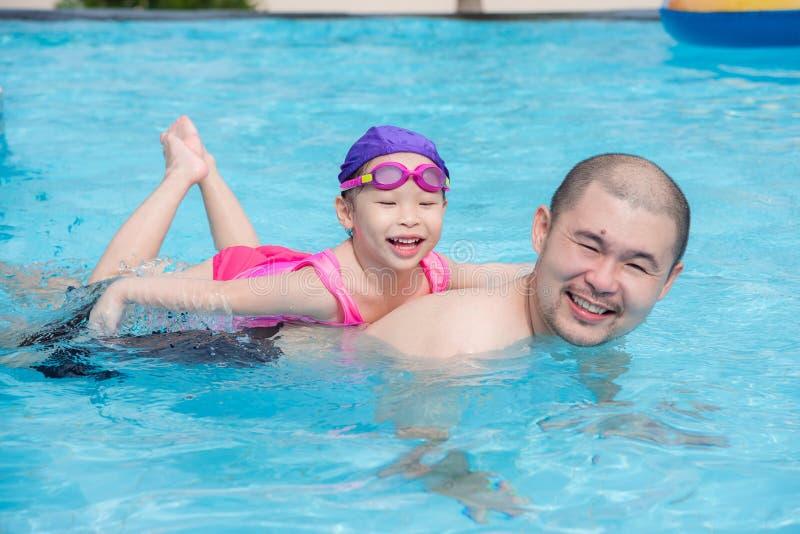 Ragazza che sorride felicemente sulla sua parte posteriore del padre nella piscina fotografie stock