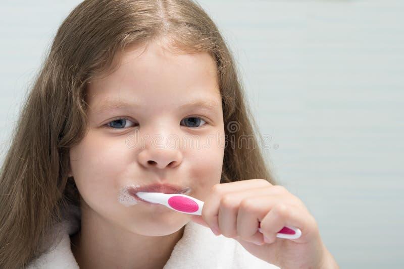 Ragazza che spazzola il suo tempo dei denti della toilette di mattina immagini stock