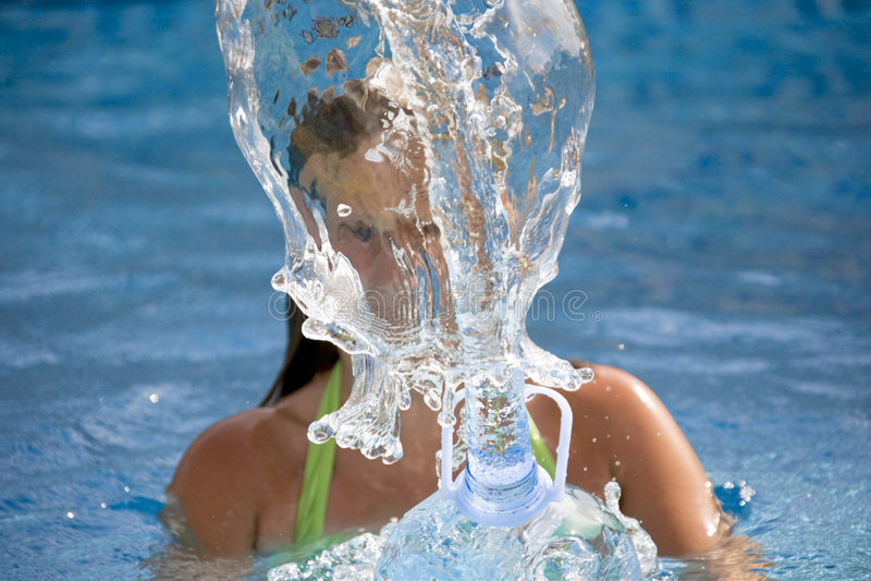 Ragazza che spruzza acqua nella piscina fotografia stock libera da diritti
