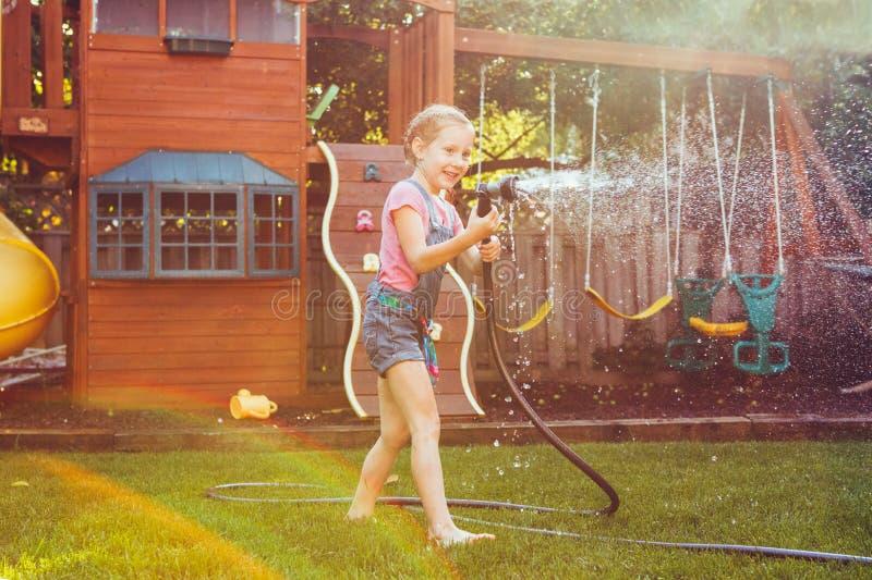 Ragazza che spruzza con la casa di giardinaggio sul cortile il giorno di estate fotografia stock