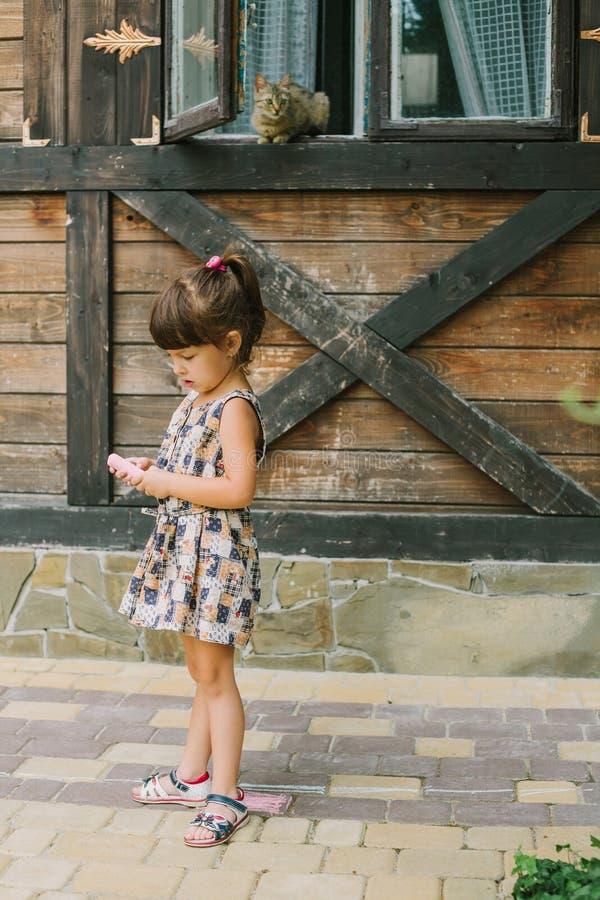 Ragazza che sta con il gesso vicino ad una casa di legno immagine stock libera da diritti