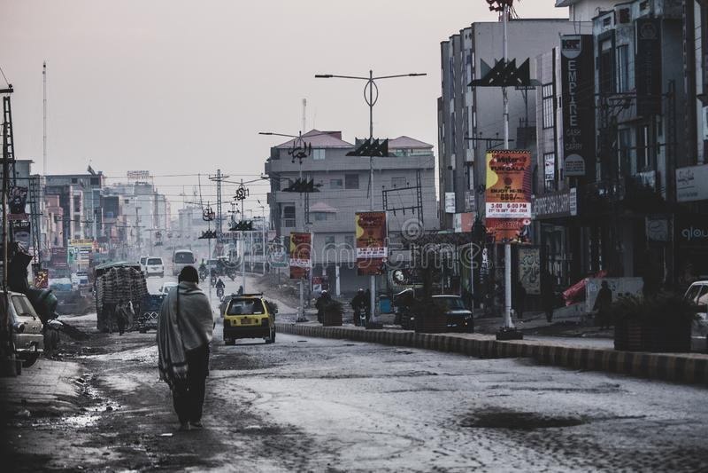 Ragazza che sta da solo nelle vie occupate e molto povere di Islamabad immagini stock libere da diritti