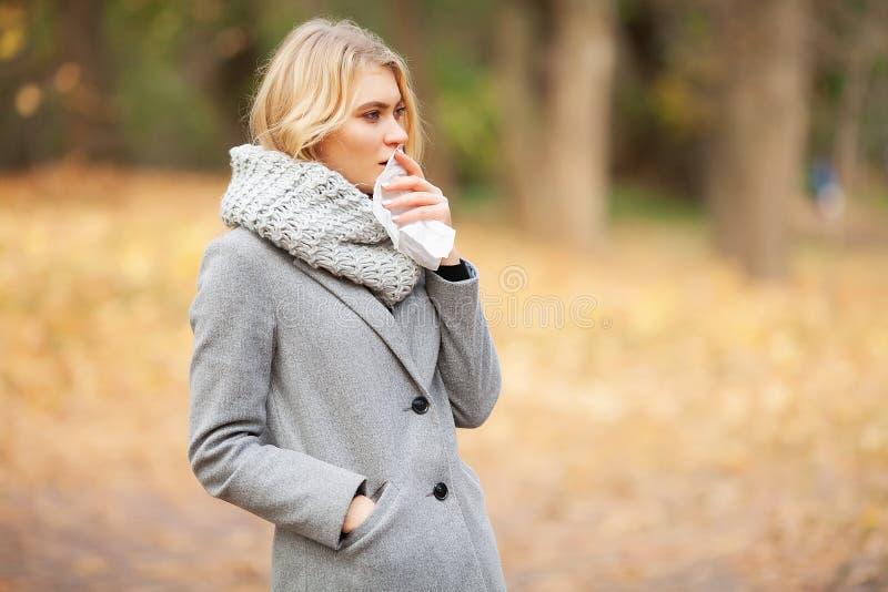 Ragazza che starnutisce nel tessuto Giovane donna che soffia il suo naso sul parco Starnuto all'aperto del ritratto della donna p fotografia stock