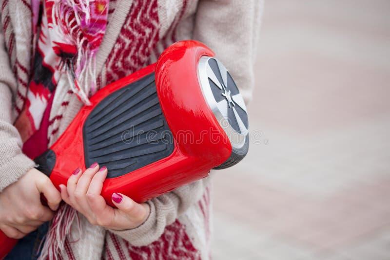 Ragazza che tiene il mini motorino elettrico rosso moderno di librazione o segway del bordo fotografia stock