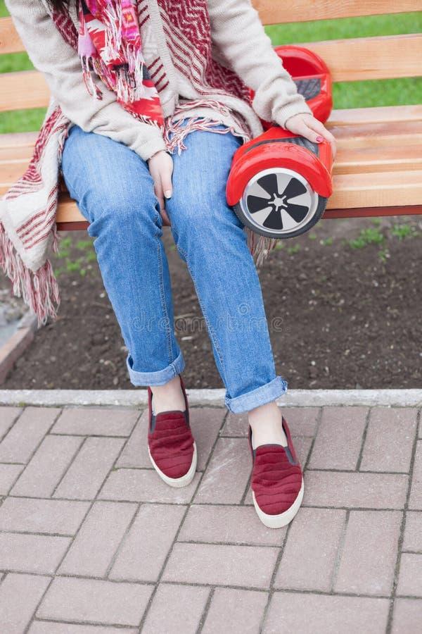 Ragazza che tiene il mini motorino elettrico rosso moderno di librazione o segway del bordo fotografia stock libera da diritti