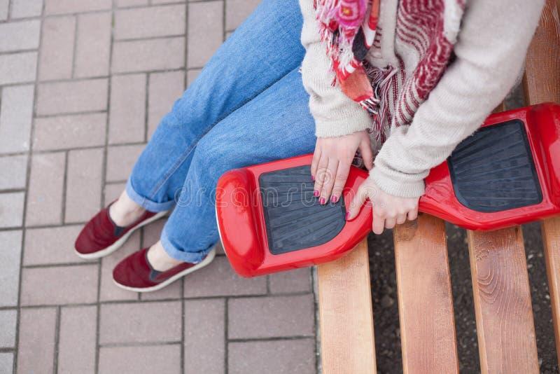 Ragazza che tiene il mini motorino elettrico rosso moderno di librazione o segway del bordo fotografie stock