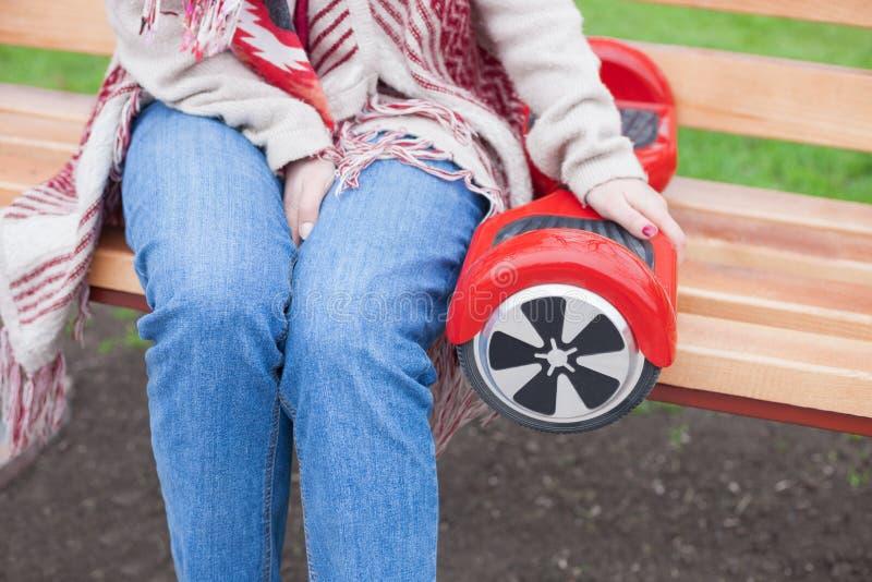 Ragazza che tiene il mini motorino elettrico rosso moderno di librazione o segway del bordo immagine stock libera da diritti
