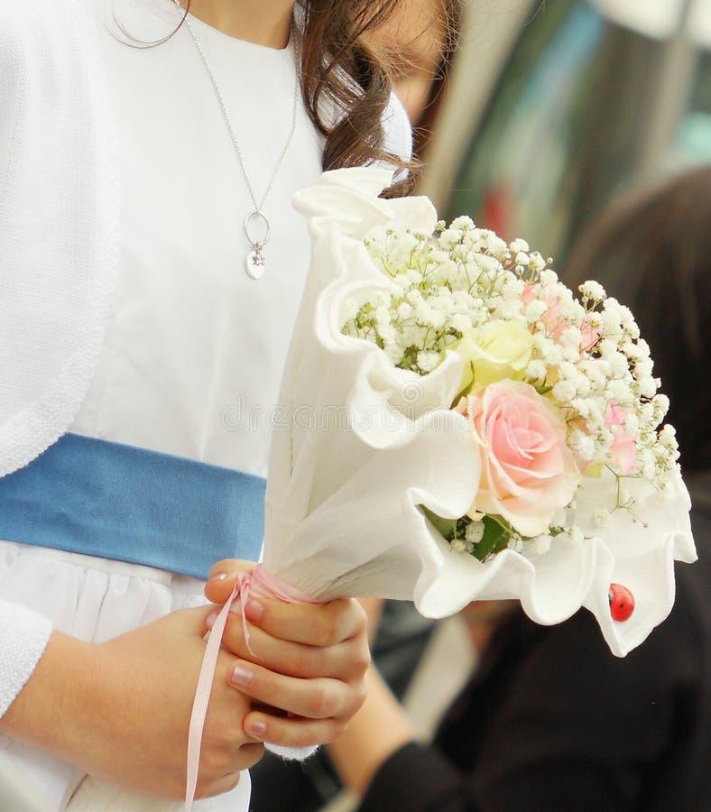 Ragazza che tiene il primo mazzo del fiore di comunione in sue mani fotografia stock