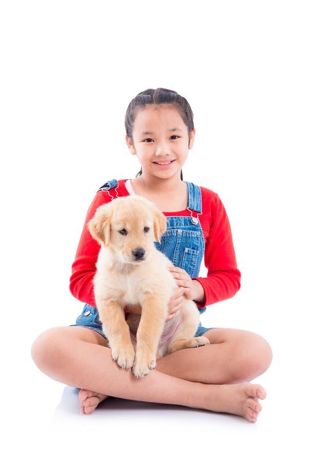 Ragazza che tiene il suoi cane e sorrisi sopra bianco fotografia stock