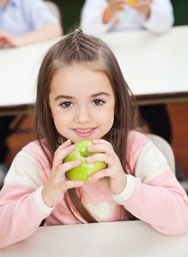 Ragazza che tiene Smith Apple With Classmates In fotografie stock