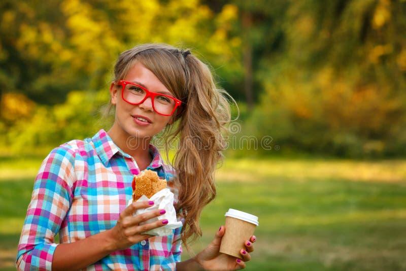 Ragazza che tiene tazza di caffè e un hot dog immagini stock