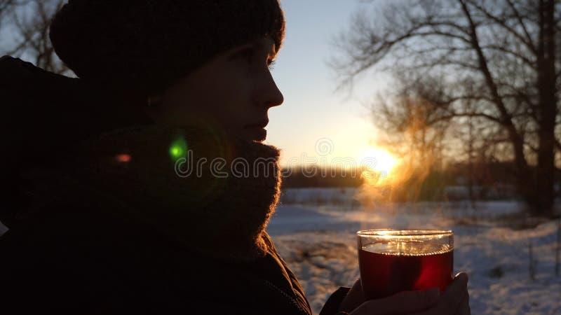 Ragazza che tiene tazza in sua mano con tè caldo da cui c'è vapore al tramonto fotografia stock